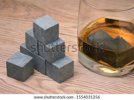 Glass with whiskey and whiskey stones on wooden background #1554031256