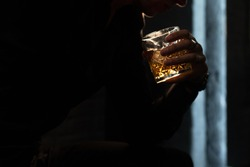 glass with whiskey brandy in a man's hand on a black background. male silhouette with a glass of whiskey on a black background