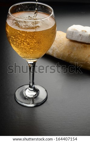 Glass with white sparkling wine/Wine Bread and Cheese/White sparkling wine with bread and cheese in the background