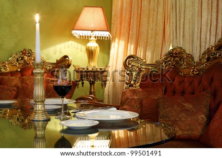 glass with wine and candlestick with candle at table, red sofa and lamp in cozy restaurant