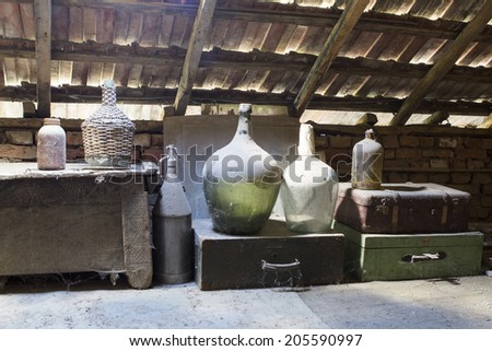 Glass, wooden and metallic objects in the attic with dust and spiderwebs in a beautiful, moody light