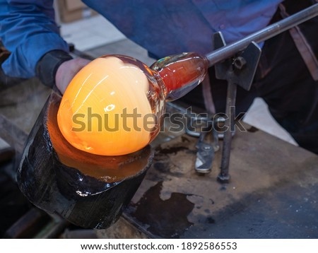 Photo of  Glassblower is using wet wooden form for shaping the red melted glass on the end of glassblowing pipe. Traditional handmade Czech glass workshop in Kunratice.