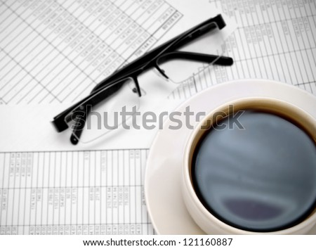 Glasses and a cup of coffee on documents.