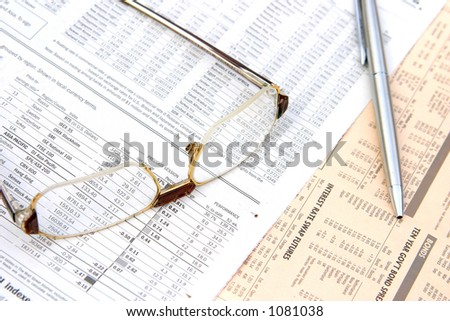 glasses and a pen on top of a financial newspaper.