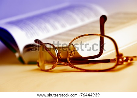 Glasses and book, extreme close-up and toned by two colors.