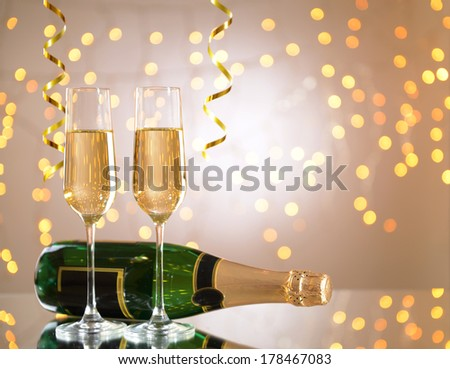 Glasses and bottle of champagne on shiny background #178467083