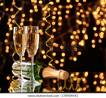 Glasses and bottle of champagne on shiny background - Shutterstock ID 178904441