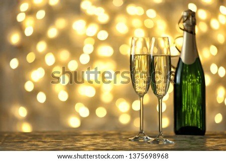 Glasses and bottle of champagne on table against blurred lights. Space for text #1375698968
