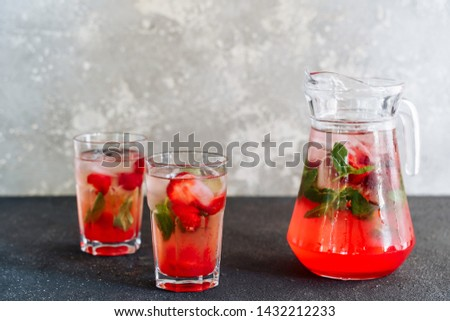 Glasses and Carafe with Fresh Strawberry Lemonade. Cold Refreshing Mixed Berries with Herbal Mint and Ice Beverage Cocktail in Cup and Decanter. Summer Juicy Vitamin Drink Side View #1432212233