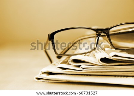 Glasses and newspaper in gold tone