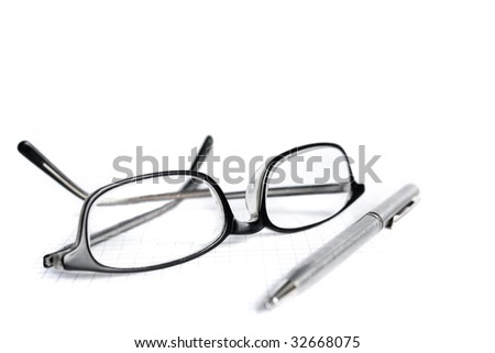 Glasses and pen isolated on white