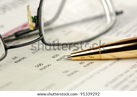 Glasses and pen lie on a newspaper