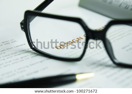 """Glasses and pen on open book ,Focus at word  """"DESIGN """"."""