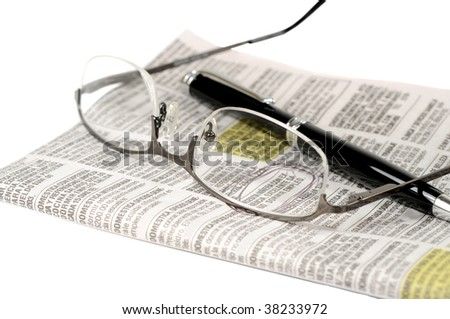 Glasses and pen over a newspaper classifieds page