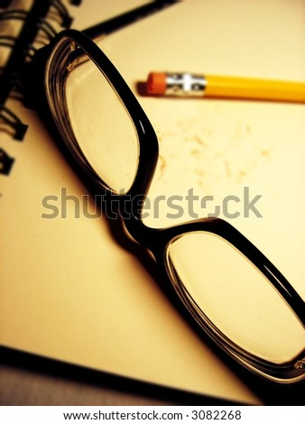 glasses and pencil on book