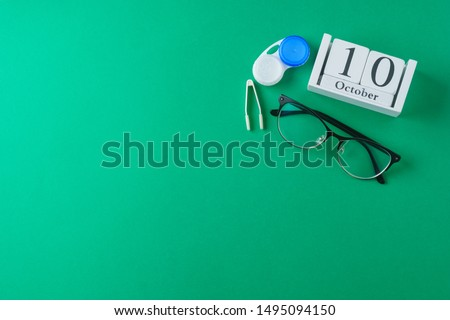 Glasses and wooden calendar, world view day, concept, on green background, top view