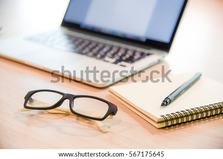 Glasses, binder notebook, pen and laptop on wooden office desk, use for background in business management and learn education concepts