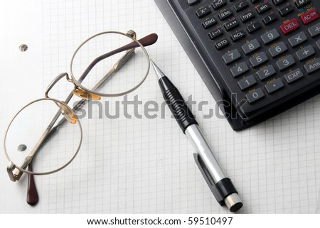 glasses, calculator and pencil on an open notebook