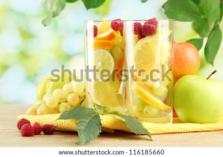 glasses citrus fruits and raspberries, on green background