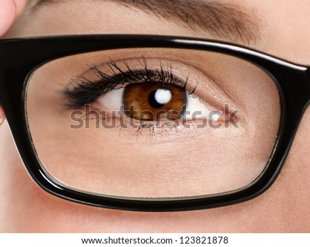 Glasses eyewear closeup. Macro of woman black eye wear glasses frame. Brown eyes of multiethnic Chinese Asian / Caucasian woman model. - stock photo