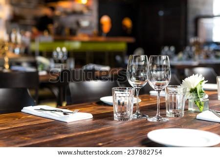 Glasses, flower fork, knife served for dinner in restaurant with cozy interior