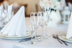 Glasses, flowers, fork, knife, napkin folded in a pyramid, served for dinner in restaurant with cozy interior. Wedding decorations and items for food, arranged by the catering service on a large table
