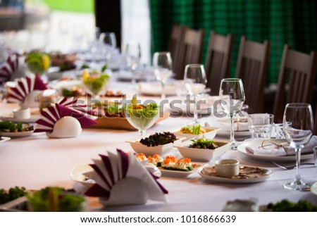 Glasses, flowers, fork, knife served for dinner in restaurant with cozy interior #1016866639