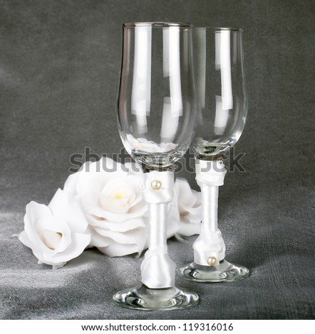 glasses for champagne wedding with the decoration of white satin and pearls are on the grey dark surface on a black background with white roses in the background
