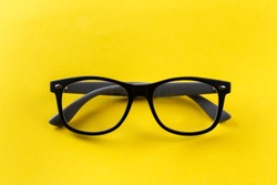 Glasses for vision in black frames on a yellow background. Short sighted and presbyopia (Farsightedness) eyeglasses.