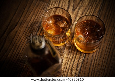 glasses from whisky and a bottle on a wooden table