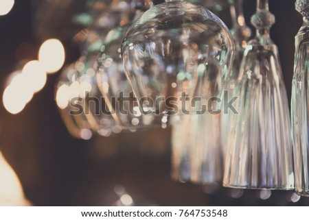 Glasses hanging on bar rack close up. Clean utensil for wine and cognac in restaurant, barroom background