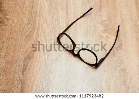 Glasses in black vintage frame on wooden background, table. View from above. #1117923482