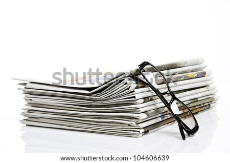 glasses lean on newspapers against white background
