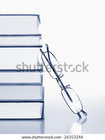 glasses leaning on a pile of books  blue-tone