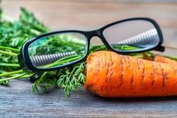 Glasses lie on fresh carrots. Effect of carrots on human eyesight