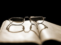 Glasses lying on a book with a shadow in the shape of a heart with backlighting