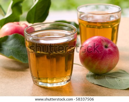 Glasses of apple juice with apples on the background.