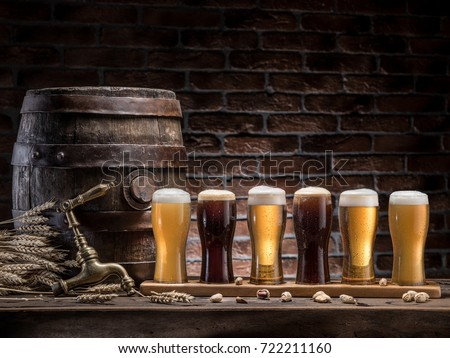 Glasses of beer and ale barrel on the wooden table. Craft brewery. Beer background.