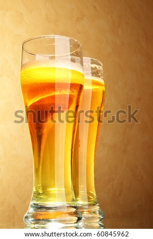 Glasses of beer with froth close-up over yellow background