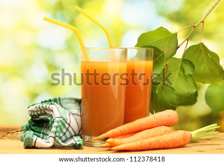 glasses of carrot juice and fresh carrots on wooden table on green background