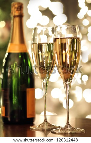 Glasses of champagne and bottle with festive background