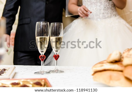 Glasses of champagne and bride and groom on background, selective focus