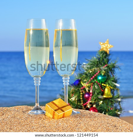 Glasses of champagne and decorated Christmas tree on the beach against the sky and blue sea