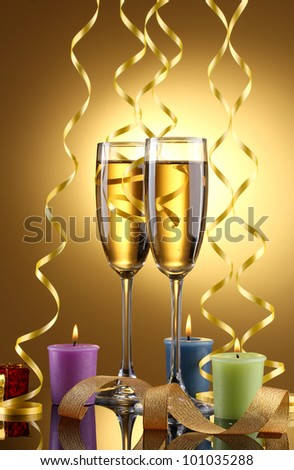 glasses of champagne, candles, gifts and streamer on yellow background