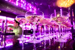 Glasses of champagne on bar counter with barman professional, which making cocktail drinks in background, soft focus