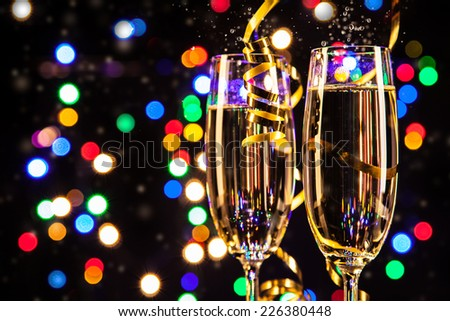 Glasses of champagne on black background with blur colored spot lights. Concept of celebration