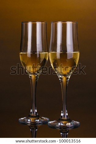 Glasses of champagne on brown background