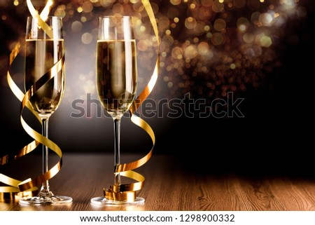 Glasses of champagne with curly ribbon  on wooden table #1298900332