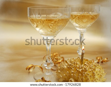 Glasses of champagne with golden candle and chrysanthemum