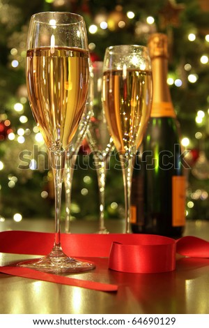 Glasses of champagne with ribbon against defocus Christmas Lights